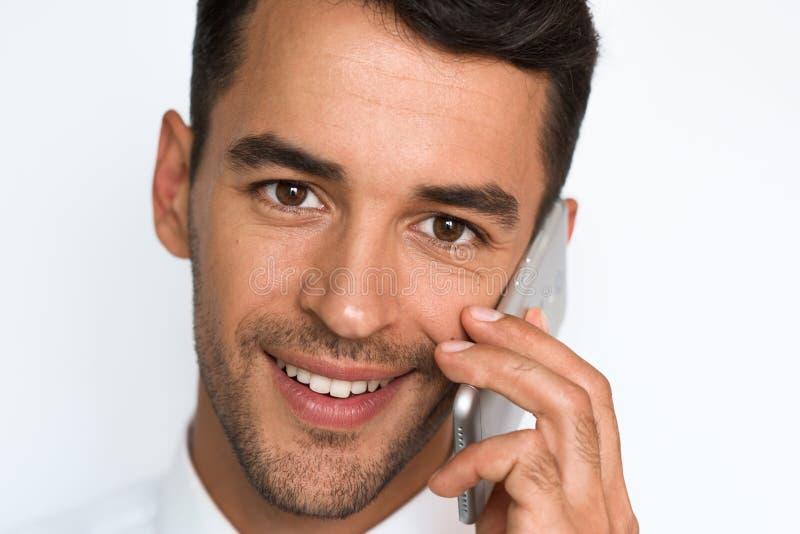 Retrato ascendente cercano del hombre joven hermoso de la sonrisa en la camisa blanca usando el teléfono móvil, mirando la cámara foto de archivo libre de regalías
