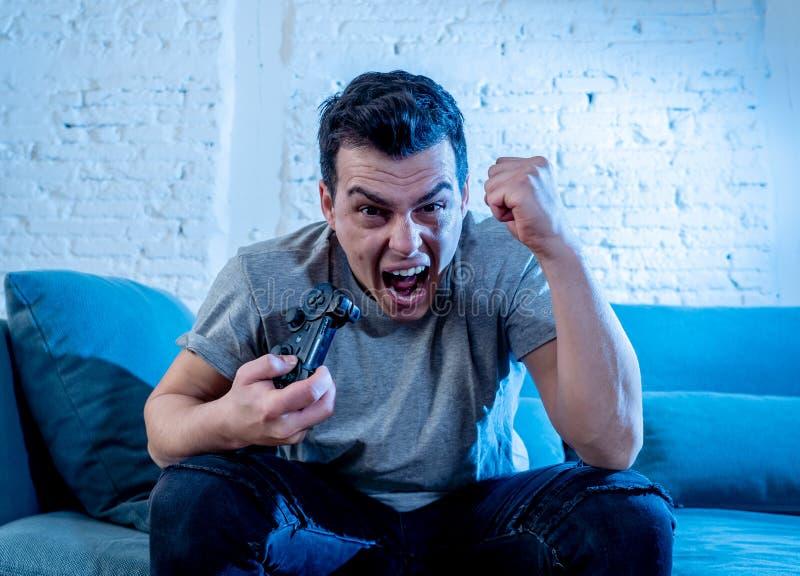 Retrato ascendente cercano del hombre joven que juega al videojuego en la noche enviciado a él que se divierte foto de archivo