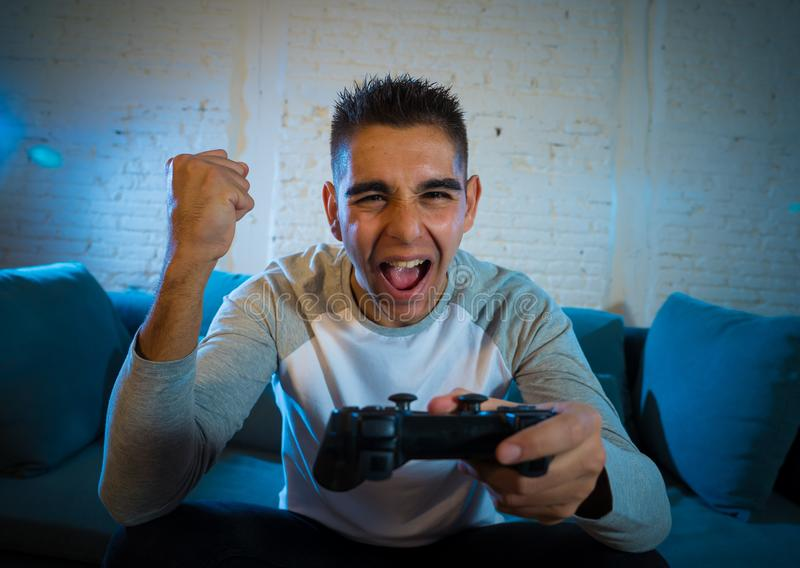 Retrato ascendente cercano del hombre joven que se divierte que juega a los videojuegos En ocio y concepto del apego del juego foto de archivo