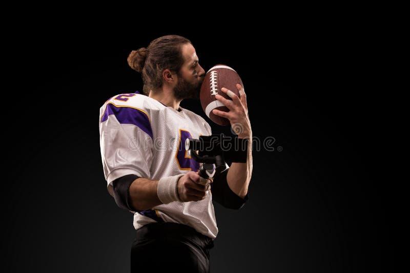Retrato ascendente cercano del jugador de f?tbol americano que besa suavemente la bola foto de archivo libre de regalías