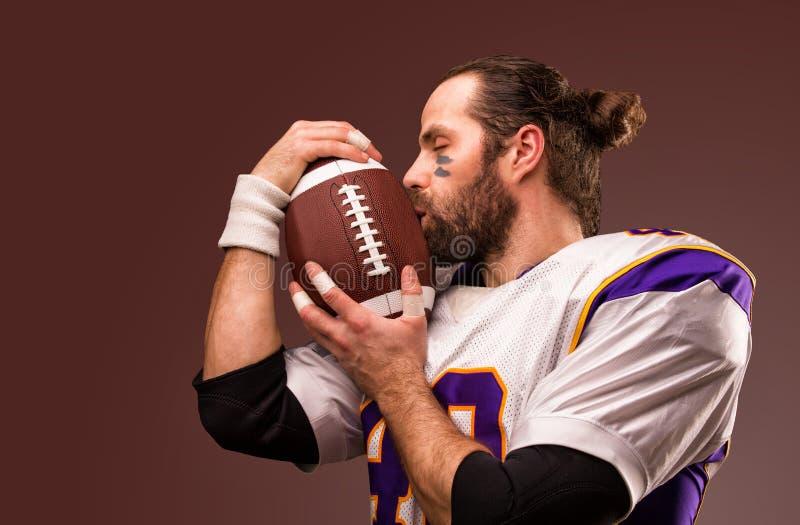 Retrato ascendente cercano del jugador de f?tbol americano que besa suavemente la bola fotografía de archivo libre de regalías