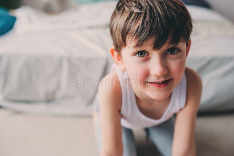 Retrato ascendente cercano del muchacho feliz lindo del niño en los pijamas que se divierten en dormitorio imágenes de archivo libres de regalías