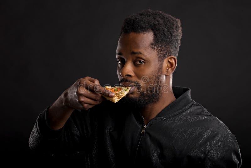 Retrato ascendente cercano del pedazo africano joven de la tenencia del hombre de pizza imágenes de archivo libres de regalías