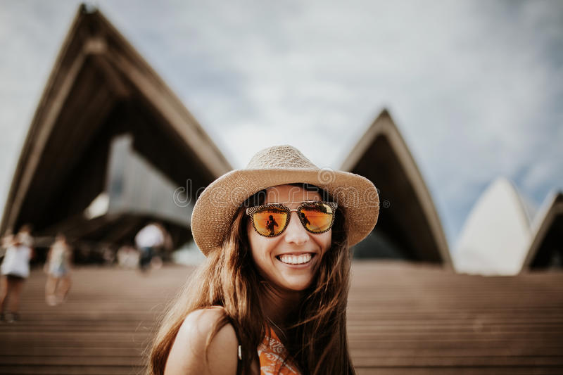 Retrato ascendente cercano sonriente lindo de la mujer, con el edificio de Sydney Opera House en el fondo imagen de archivo