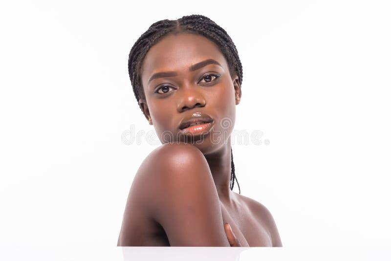 Retrato ascendente próximo da beleza de uma metade bonita africana da mulher despida que aplica o creme de cara e que olha isolad fotos de stock royalty free