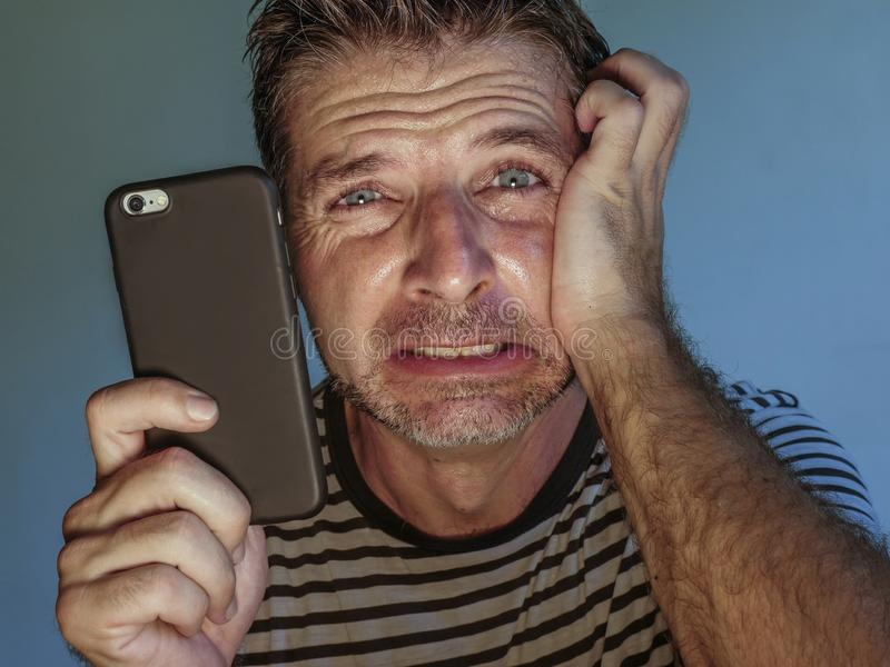 Retrato ascendente próximo da cara do homem assustado e forçado novo que usa o telefone celular que olha sentimento confuso preoc imagens de stock