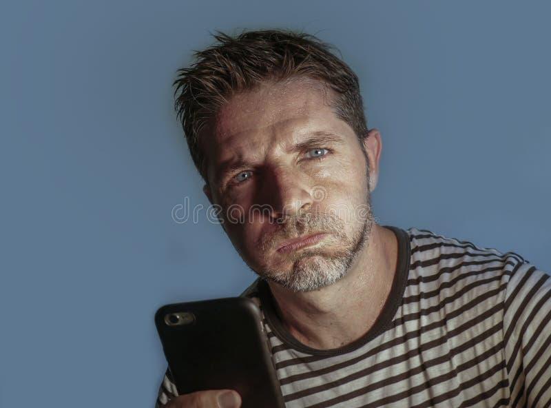 Retrato ascendente próximo da cara do homem atrativo e forçado novo que usa o sentimento do telefone celular preocupado e frustra imagens de stock