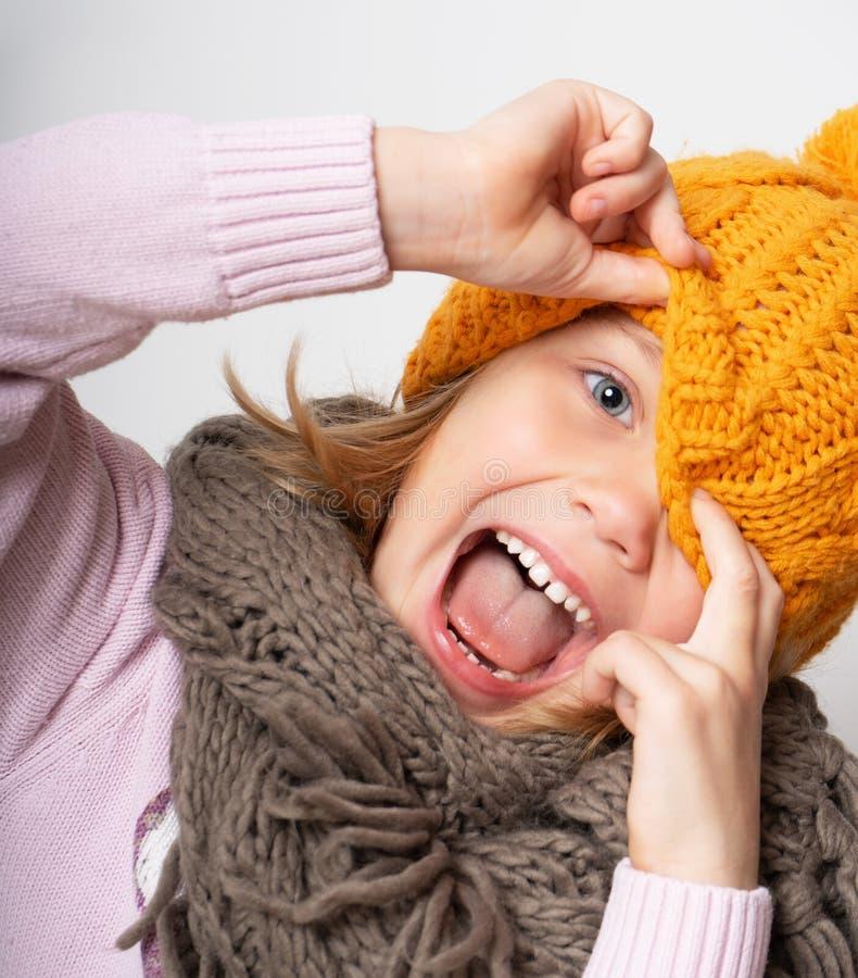 Retrato ascendente próximo da cara da jovem mulher de sorriso toothy que veste o chapéu e o lenço feitos malha fotografia de stock