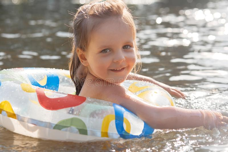 Retrato ascendente próximo da criança alegre brincalhão que sorri sinceramente, tendo a expressão facial agradável, olhando diret imagens de stock