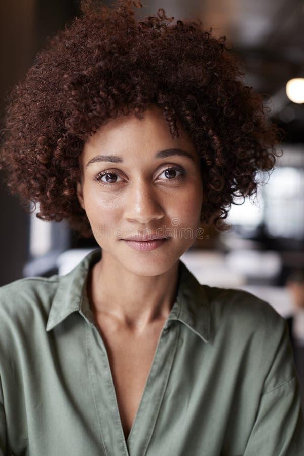 Retrato ascendente próximo da fêmea preta milenar criativa em um escritório que sorri levemente à câmera fotografia de stock