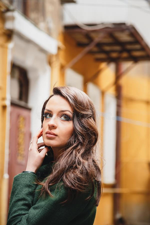 Retrato ascendente próximo da jovem mulher atrativa romântica elegante no revestimento verde na rua velha pequena da cidade fotografia de stock royalty free