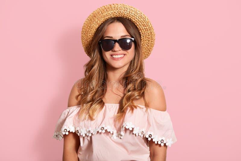Retrato ascendente próximo da jovem mulher bonita com sorriso toothy, estando em óculos de sol pretos, em camisa com ombros desen imagem de stock