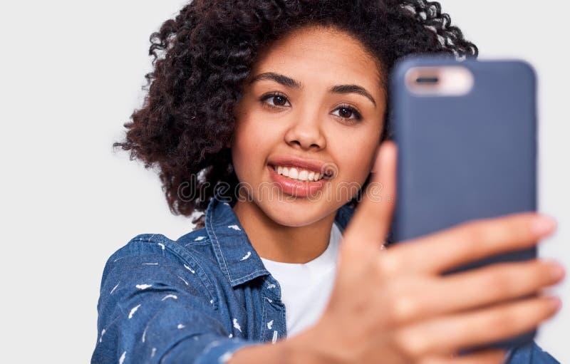 Retrato ascendente próximo da jovem mulher descascada escura bonita no t-shirt branco e na camisa azul, tomando o selfie sobre a  imagem de stock
