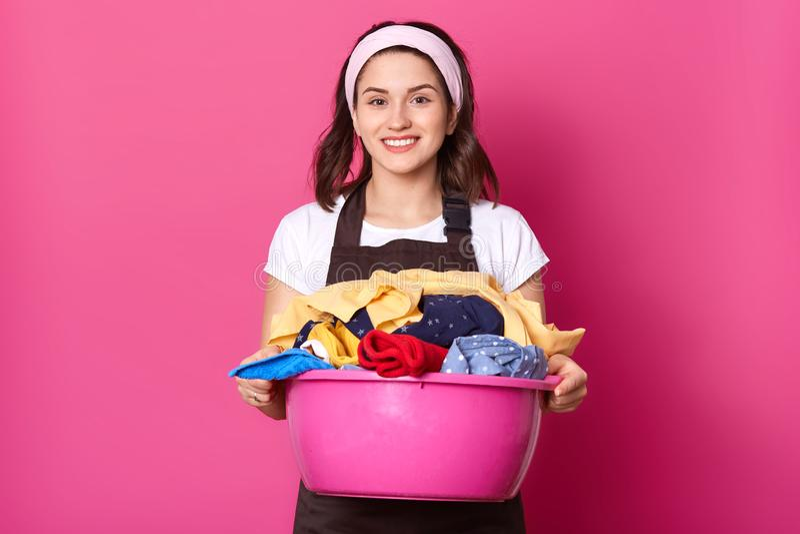 Retrato ascendente próximo da jovem senhora ocupada que levanta com bacia da lavanderia, olhando diretamente na câmera, sendo s imagens de stock