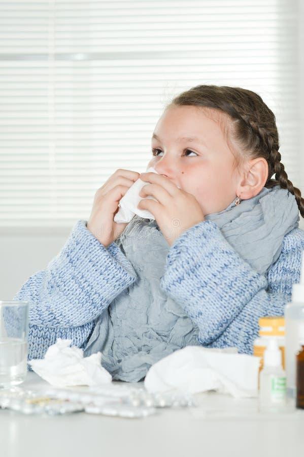 Retrato ascendente próximo da menina doente nova com as medicinas que sentam-se na tabela foto de stock royalty free