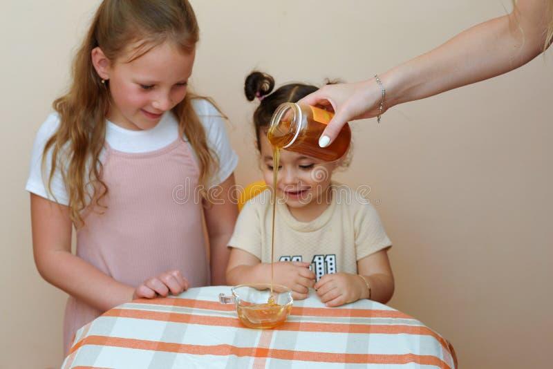 Retrato ascendente próximo da menina dois bonito engraçada que olha na mão da mulher que derrama o mel fresco do frasco na bacia imagens de stock