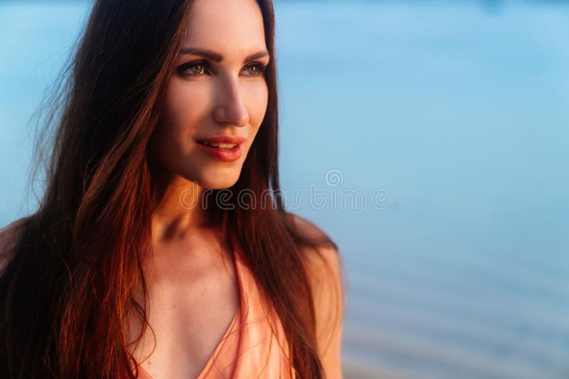 Retrato ascendente próximo da menina moreno bonita com composição no por do sol na praia do oceano imagem de stock