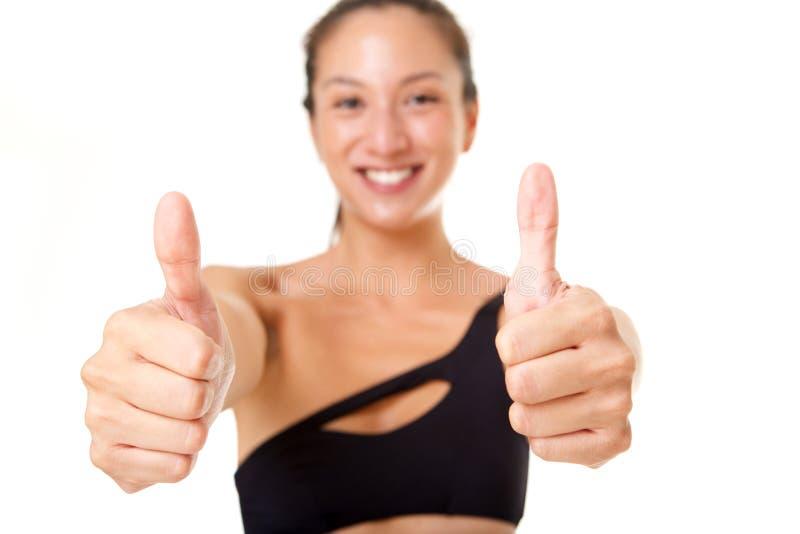 Retrato ascendente próximo da mulher asiática nova feliz com os polegares acima do sinal da mão imagem de stock