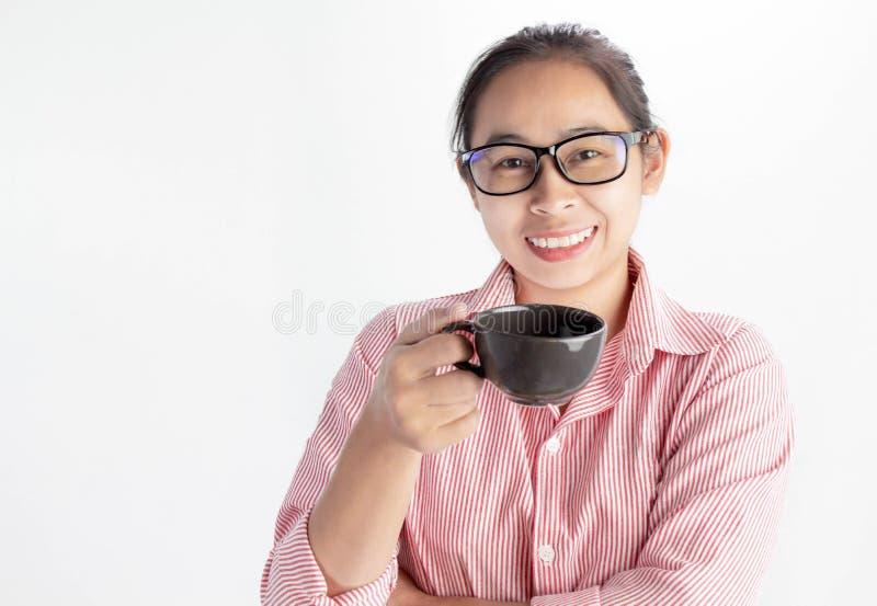 Retrato ascendente próximo da mulher asiática segura, de vidros vestindo e de guardar o copo de café, olhando a câmera e o sorris fotografia de stock