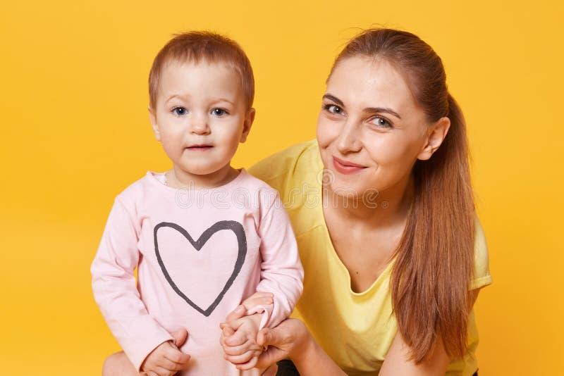 Retrato ascendente próximo da mulher caucasiano nova bonita com seu doughter, menina que veste a camisa cor-de-rosa com coração,  fotos de stock royalty free