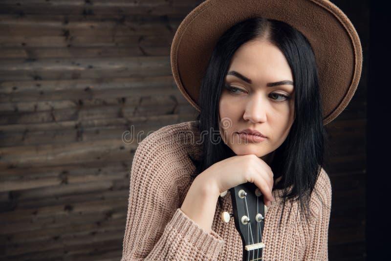 Retrato ascendente próximo da mulher caucasiano nova que joga a uquelele na frente de um fundo de madeira Tiro do estúdio, lazer fotografia de stock