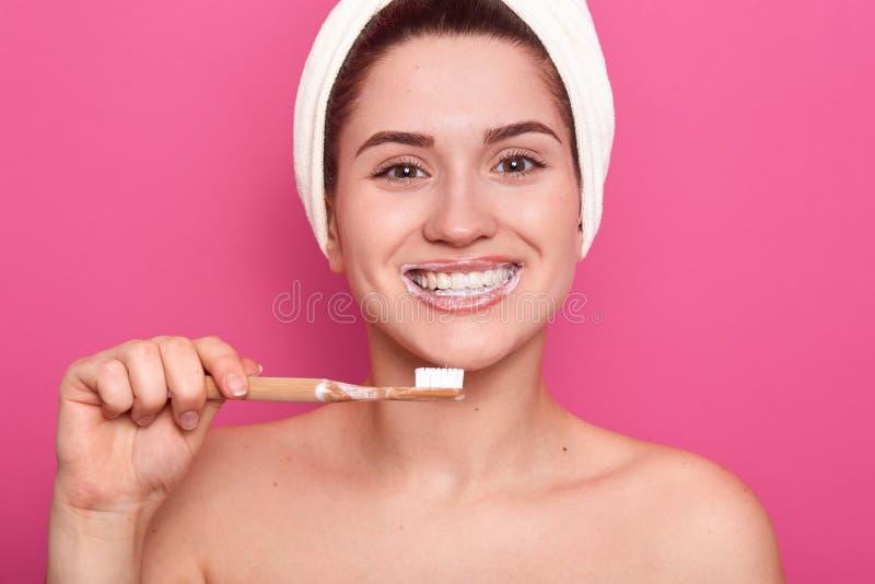 Retrato ascendente próximo da mulher de cabelo escura de sorriso caucasiano atrativa no estúdio cor-de-rosa, levantando com a toa fotos de stock
