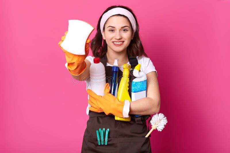 Retrato ascendente próximo da mulher de sorriso da empregada que guarda garrafas com líquido do líquido de limpeza e esponja da m imagens de stock