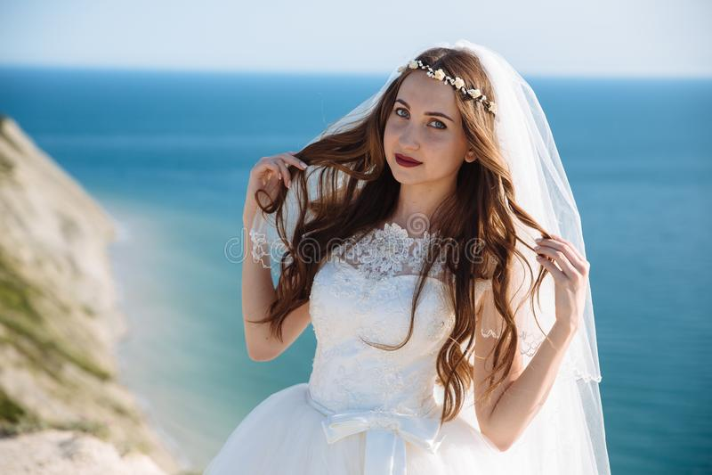 Retrato ascendente próximo da noiva bonita com véu, composição do casamento, penteado e grinalda da joia no cabelo encaracolado l fotografia de stock royalty free