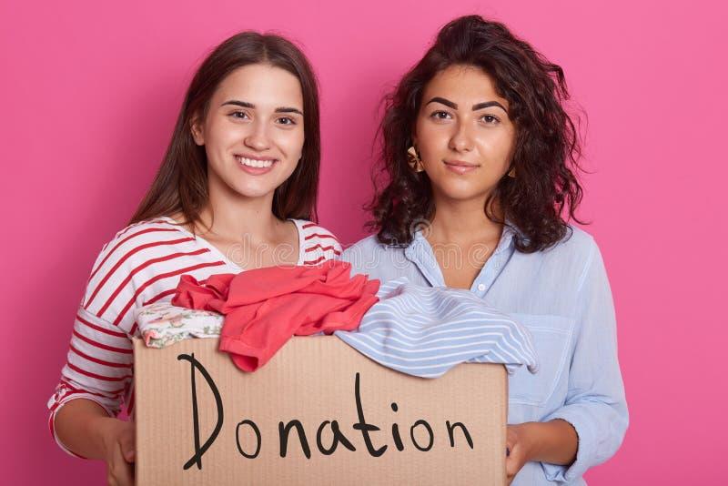 Retrato ascendente próximo de duas meninas que oferecem-se, mulheres que guardam a caixa de papel com roupa para povos pobres, am fotos de stock royalty free