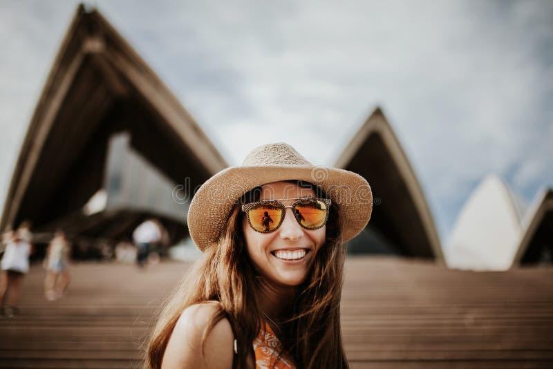 Retrato ascendente próximo de sorriso bonito da mulher, com construção de Sydney Opera House no fundo imagem de stock