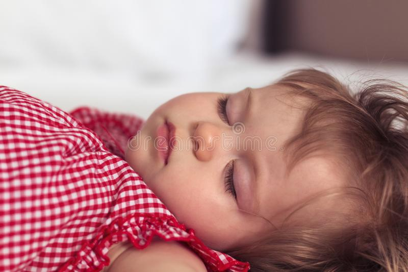 Retrato ascendente próximo de um bebê idoso bonito de nove meses que dorme no fundo borrado Cara da criança do sono cute fotografia de stock royalty free