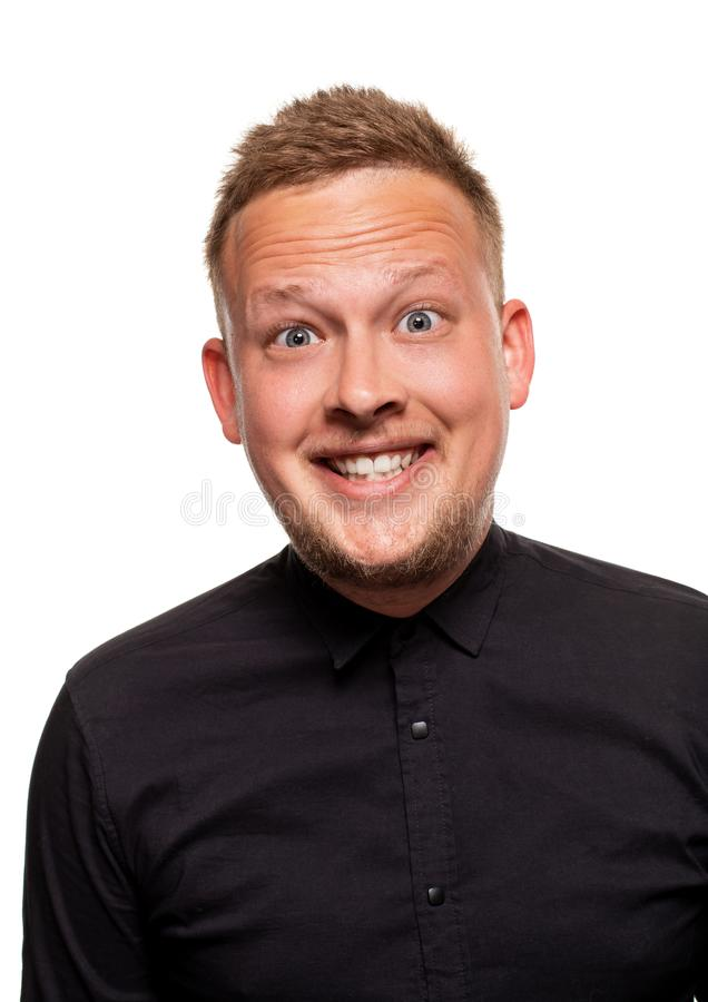 Retrato ascendente próximo de um homem novo seguro, louro, considerável que veste a camisa preta, isolada no fundo branco fotos de stock