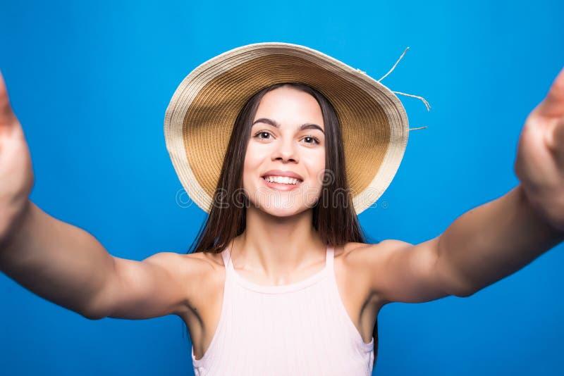 Retrato ascendente próximo de uma jovem mulher bonita no vestido do verão e no chapéu de palha que tomam um selfie isolado sobre  fotografia de stock