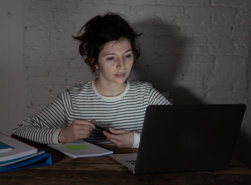 Retrato ascendente próximo de uma jovem mulher sobrecarregado e cansado que estuda tarde na noite na luz temperamental imagens de stock