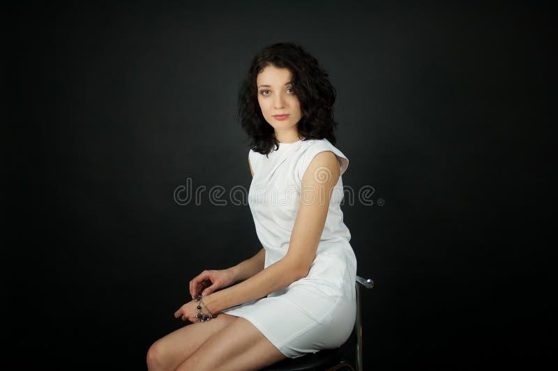 Retrato ascendente próximo do estúdio da jovem mulher bonita com composição da noite no vestido curto branco que senta-se na cade fotografia de stock