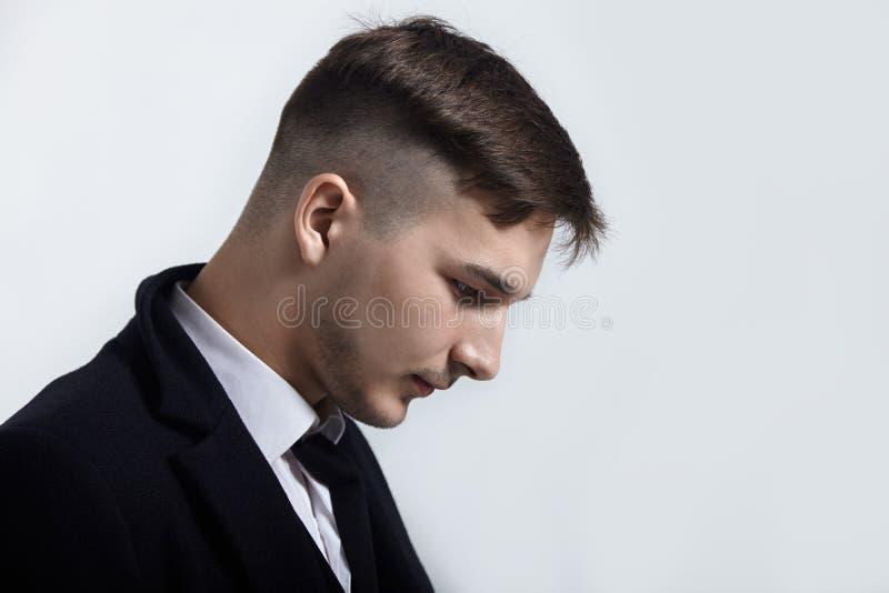 Retrato ascendente próximo do homem considerável novo no fundo claro Penteado na moda, olhar expressivo, barba pequena, terno pre foto de stock royalty free
