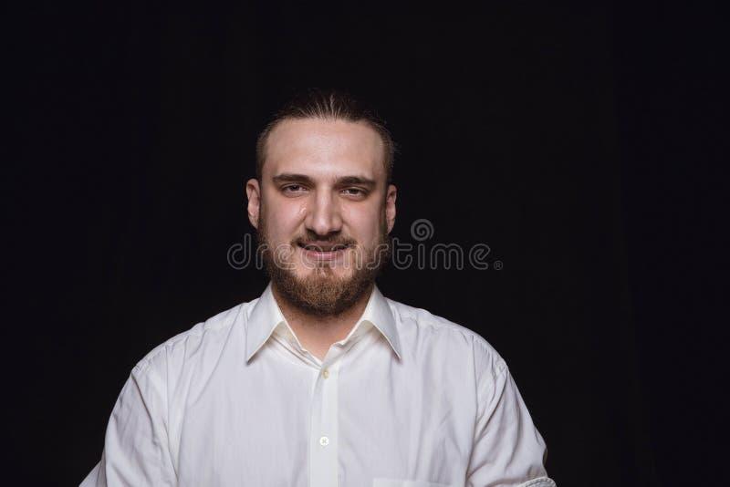 Retrato ascendente próximo do homem novo isolado no fundo preto do estúdio fotos de stock royalty free