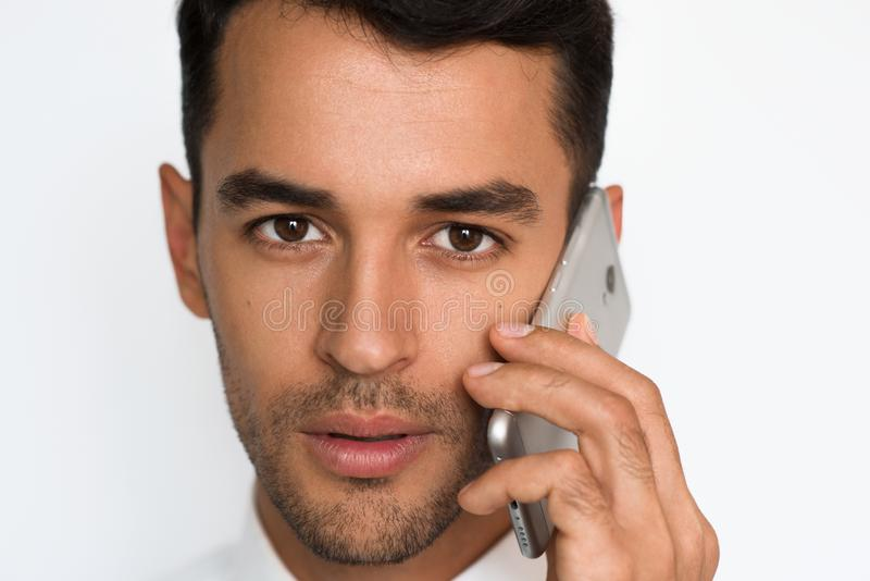 Retrato ascendente próximo do homem novo na camisa branca usando o telefone celular, olhando a câmera com expressão séria e conce imagens de stock royalty free