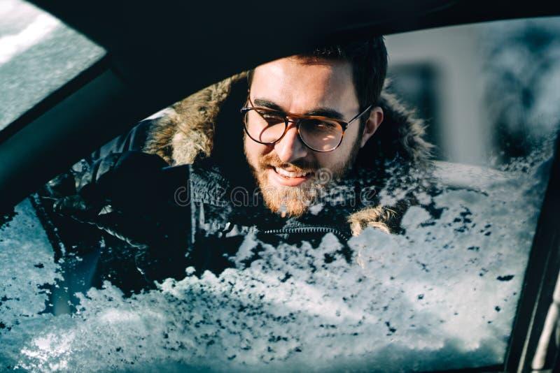 Retrato ascendente próximo do homem que usa o raspador para limpar para fora janelas de carro Transporte do inverno e conceito do fotos de stock