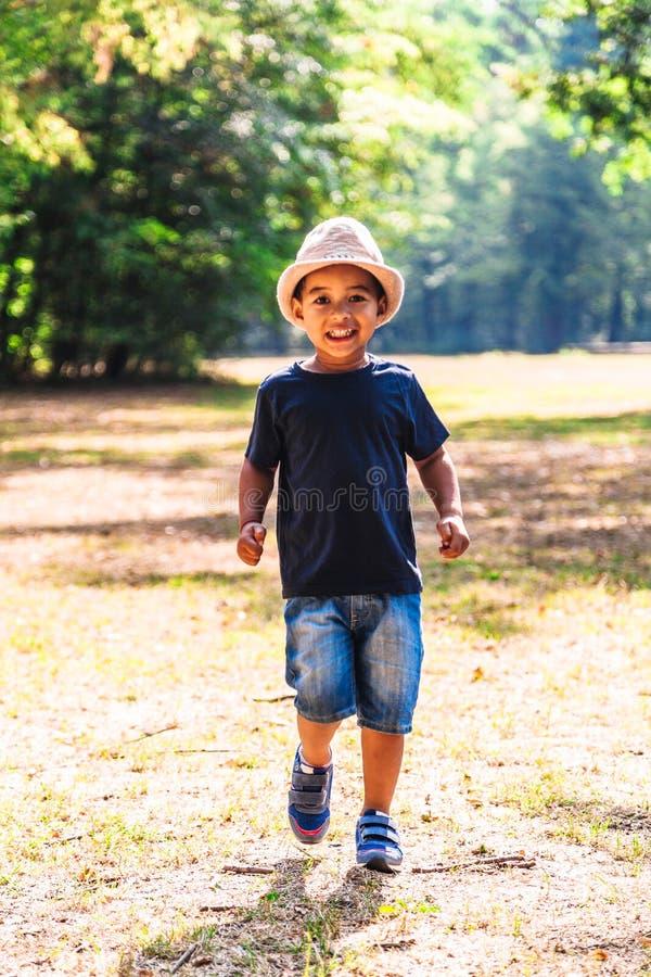 Retrato ascendente próximo do rapaz pequeno que corre fora no parque fotografia de stock