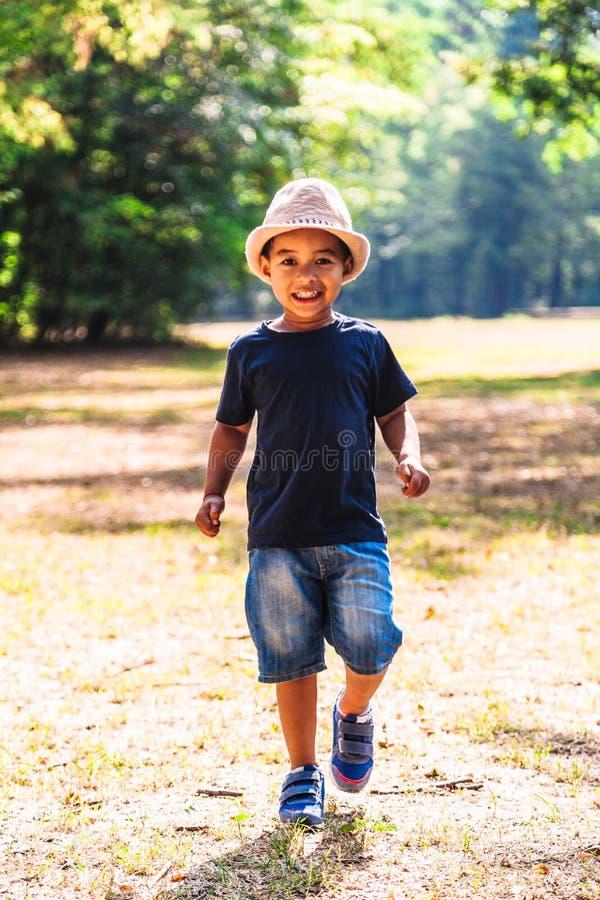 Retrato ascendente próximo do rapaz pequeno que corre fora no parque foto de stock