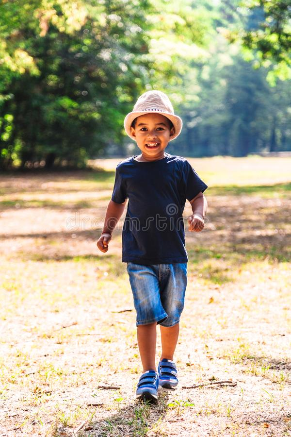 Retrato ascendente próximo do rapaz pequeno que corre fora no parque fotos de stock royalty free