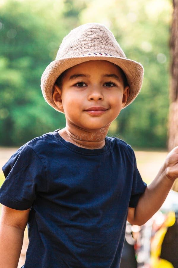 Retrato ascendente próximo do rapaz pequeno que sorri com chapéu fora fotografia de stock