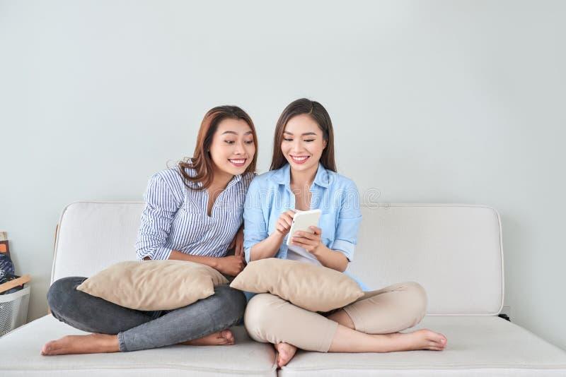 Retrato ascendente pr?ximo de duas amigas entusiasmados com telefones celulares, rindo imagem de stock
