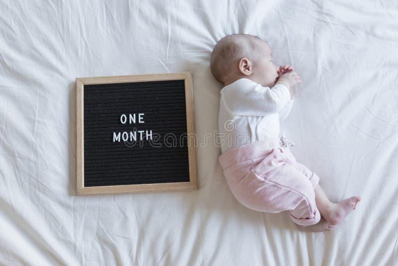 Retrato ascendente pr?ximo de um beb? bonito no fundo branco em casa vintage da placa da letra com uma mensagem do mês fotografia de stock royalty free