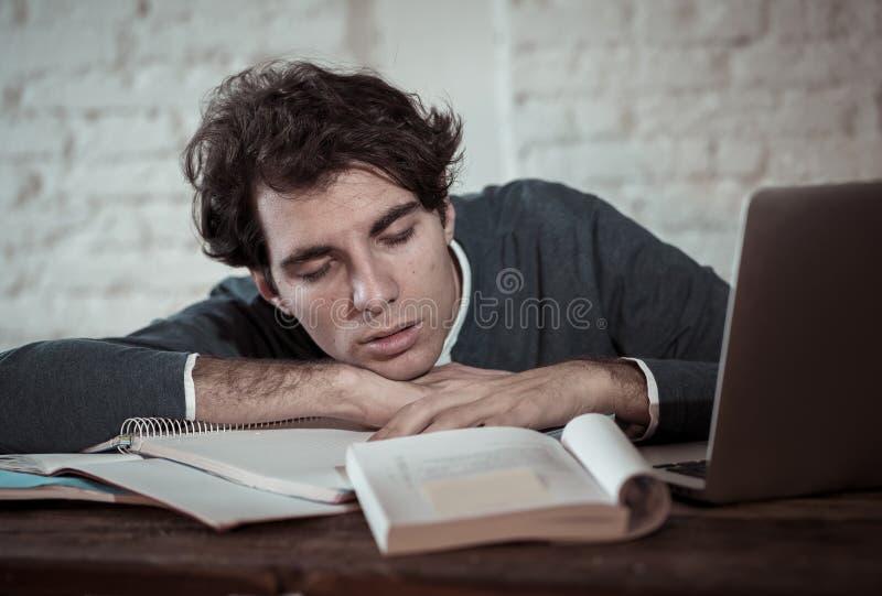 Retrato ascendente pr?ximo de um homem novo sobrecarregado e cansado que estuda tarde na noite na luz temperamental foto de stock