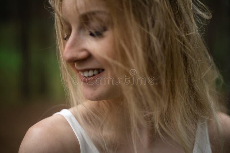 Retrato ascendente pr?ximo - ninfa loura nova bonita da floresta da mulher no vestido branco na madeira sempre-verde fotos de stock royalty free