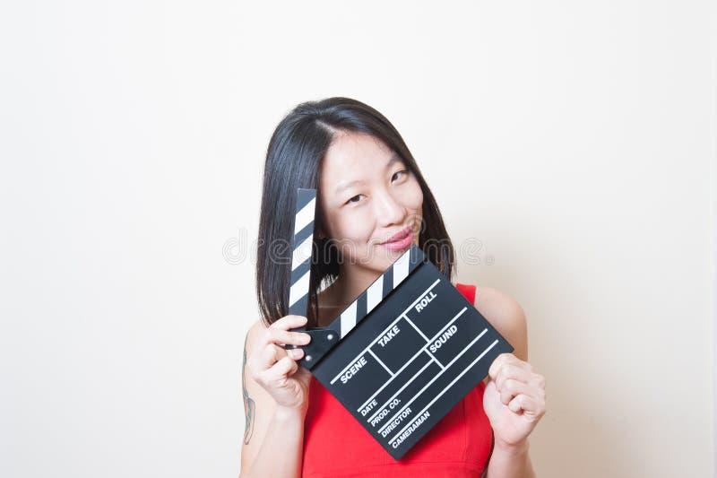 Retrato asiático hermoso joven de la mujer que presenta con clapperboard fotografía de archivo