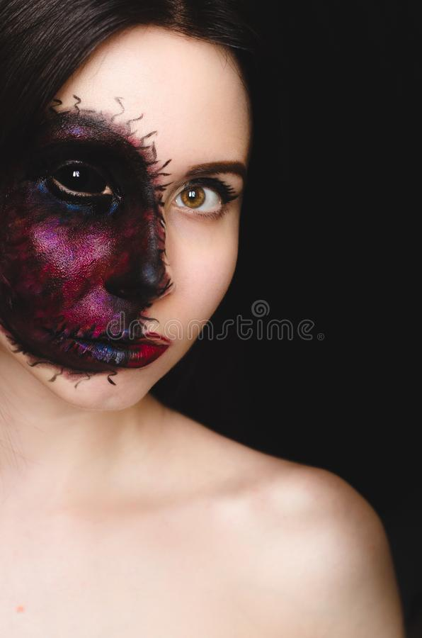 Retrato assustador de uma mulher com uma marca maldita em sua cara no fundo escuro fotos de stock royalty free