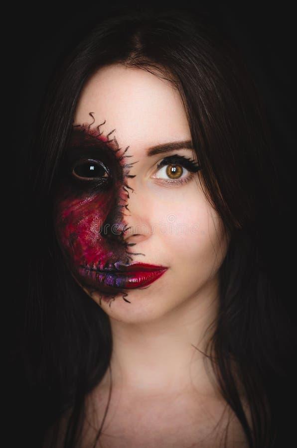 Retrato assustador de uma mulher com uma marca maldita em sua cara no fundo escuro fotos de stock